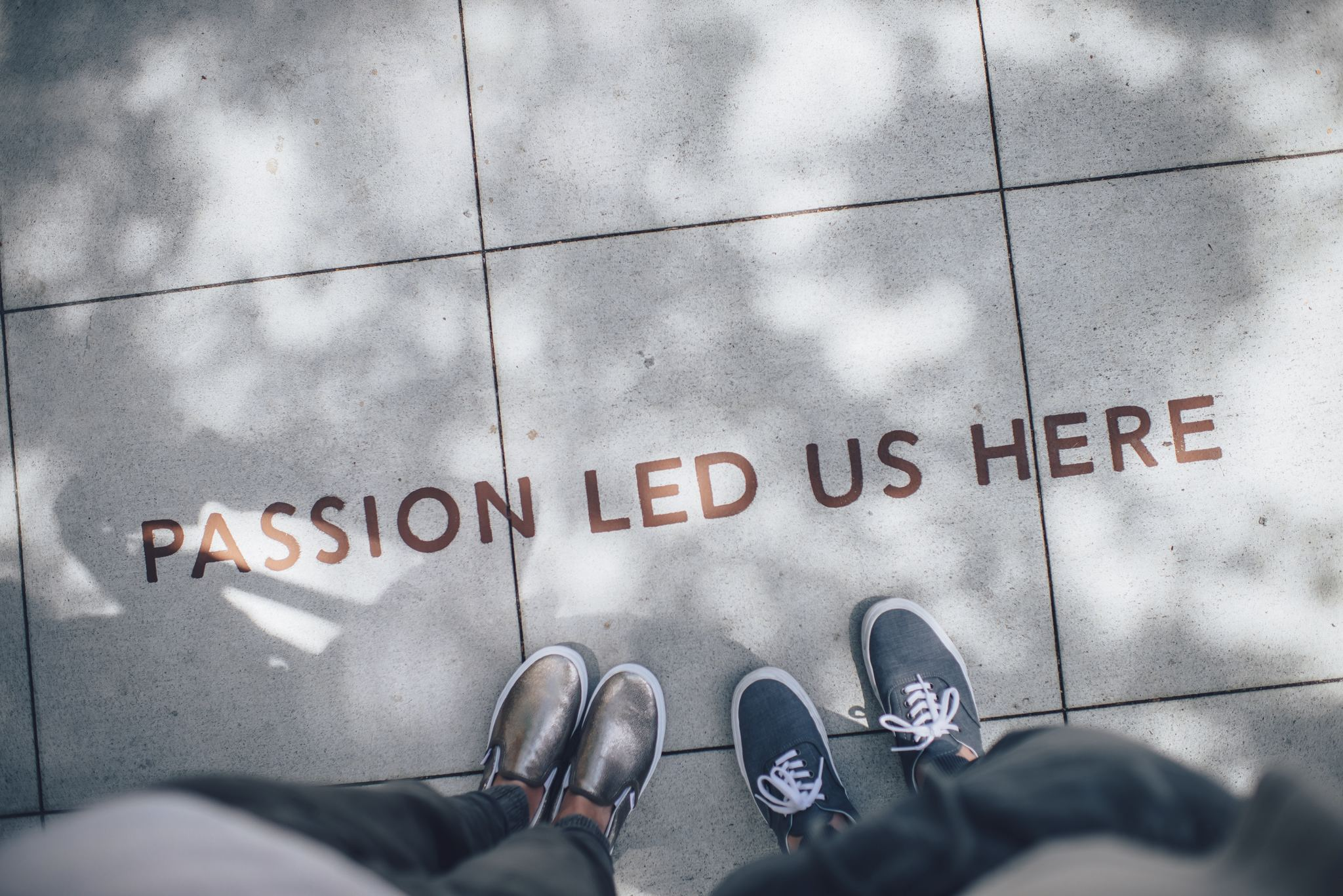 Feet on sidewalk, Passion Led Us here in black text