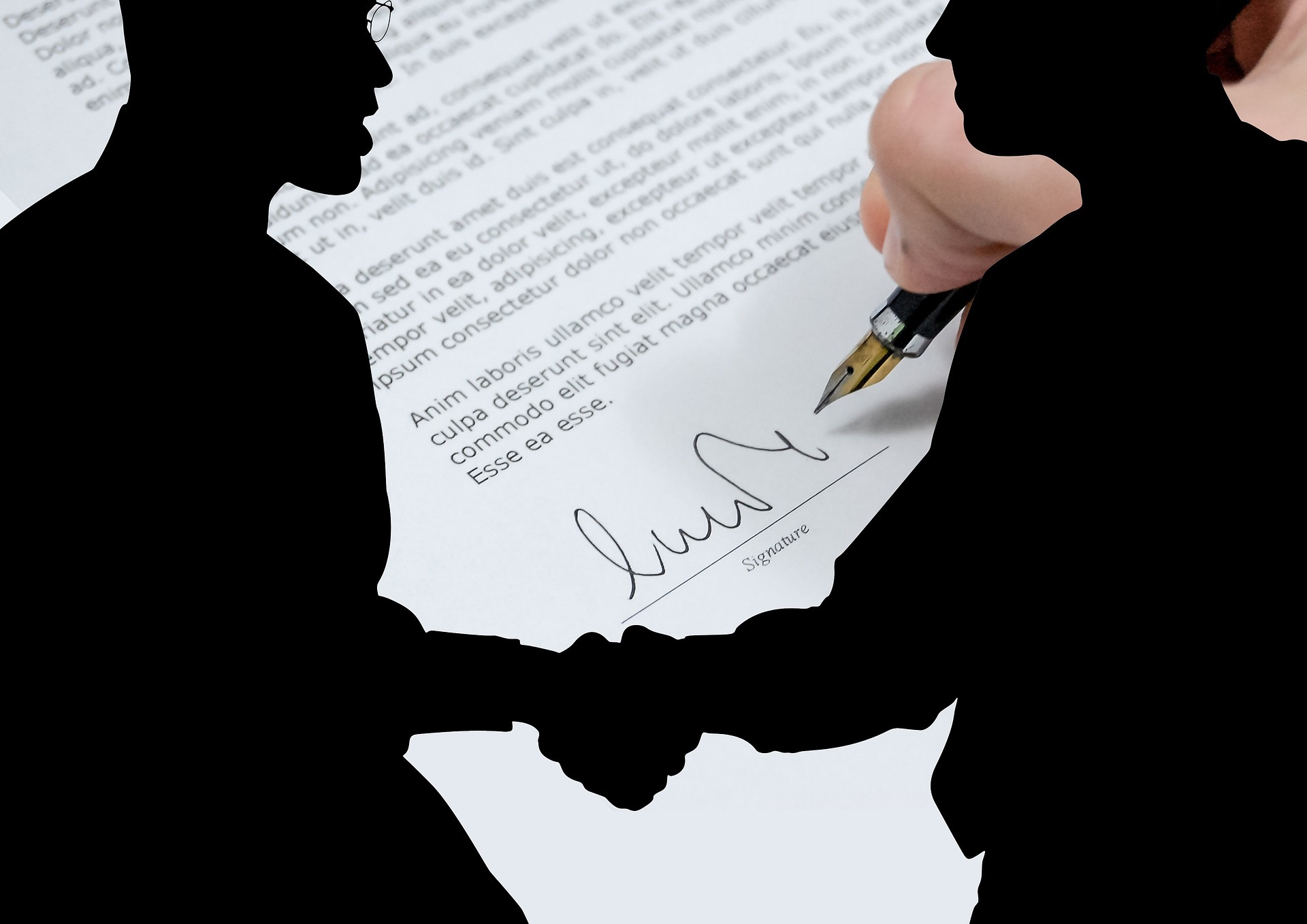 Two shadow figures shaking hands in front of a signed document